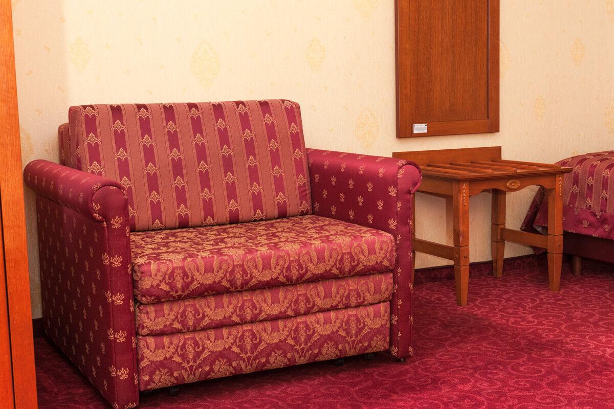fotele i stolik w pokoju czteroosobowym